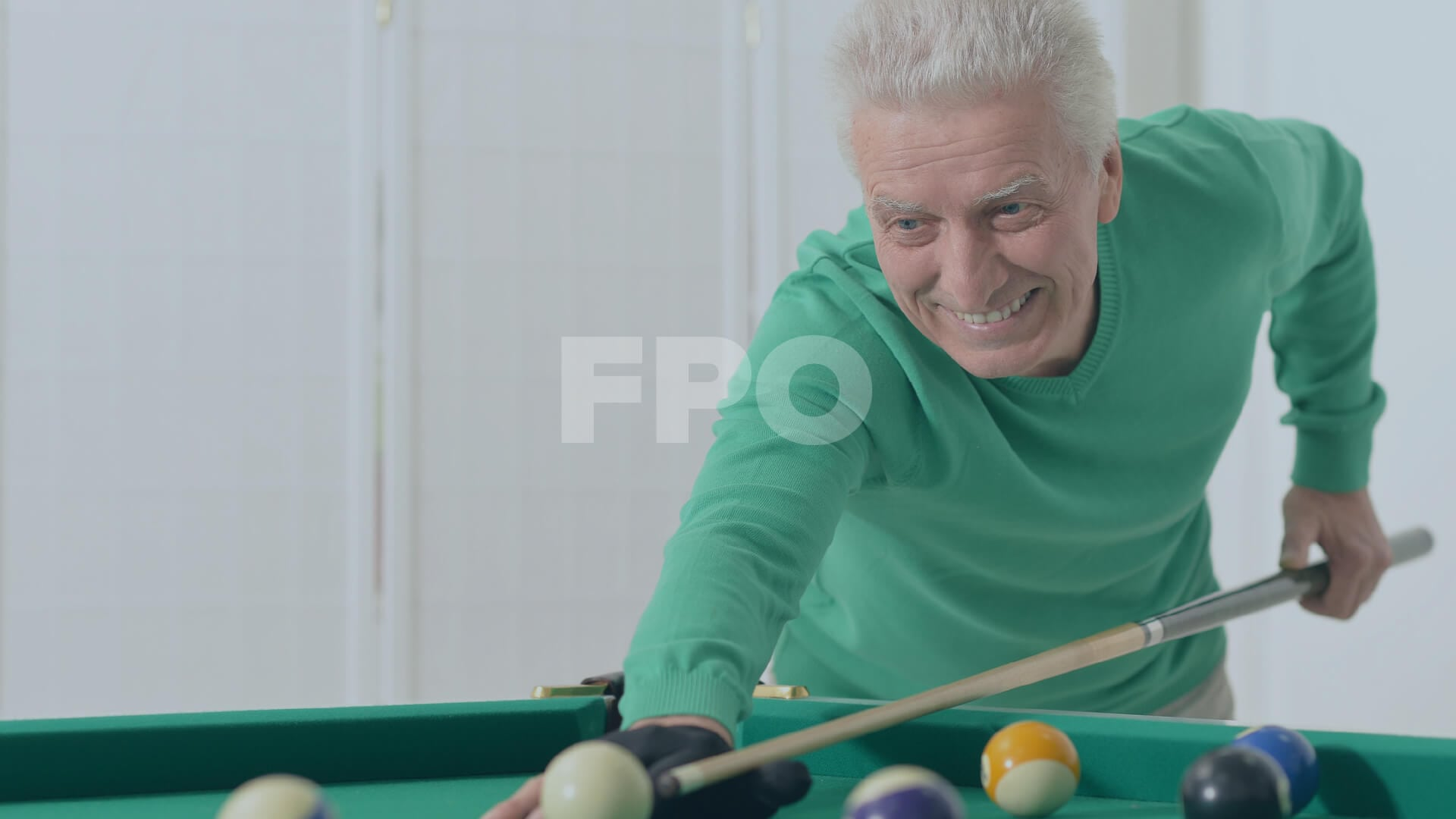 senior-aged man playing pool and smiling