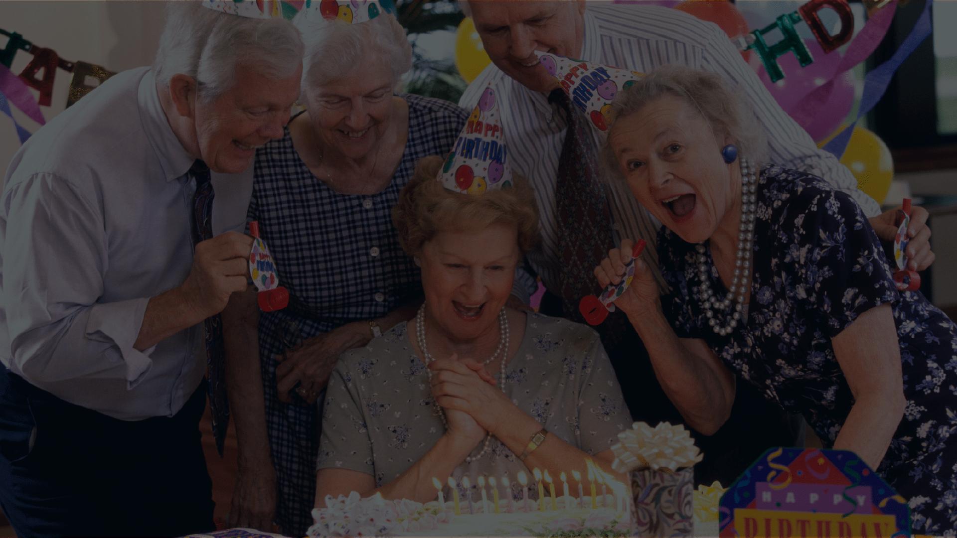 seniors celebrating birthday for friend in group