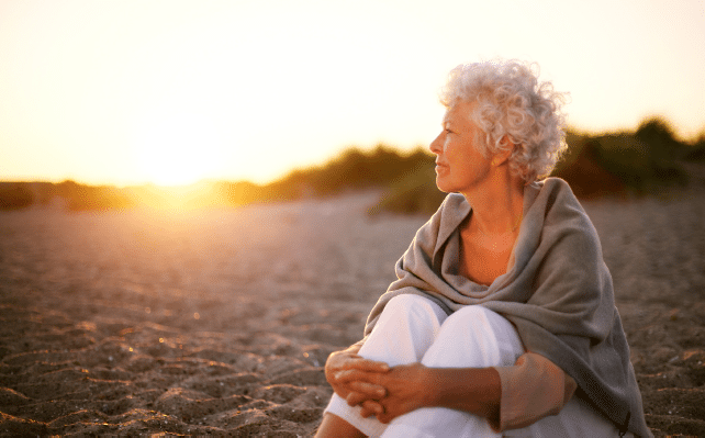 senior-aged woman sitting on beach at sunrise